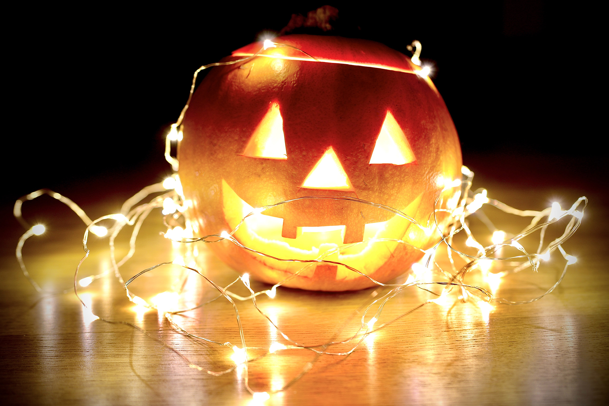 A Halloween jack-o-lantern with a smiling face and tangled in twinkling lights.