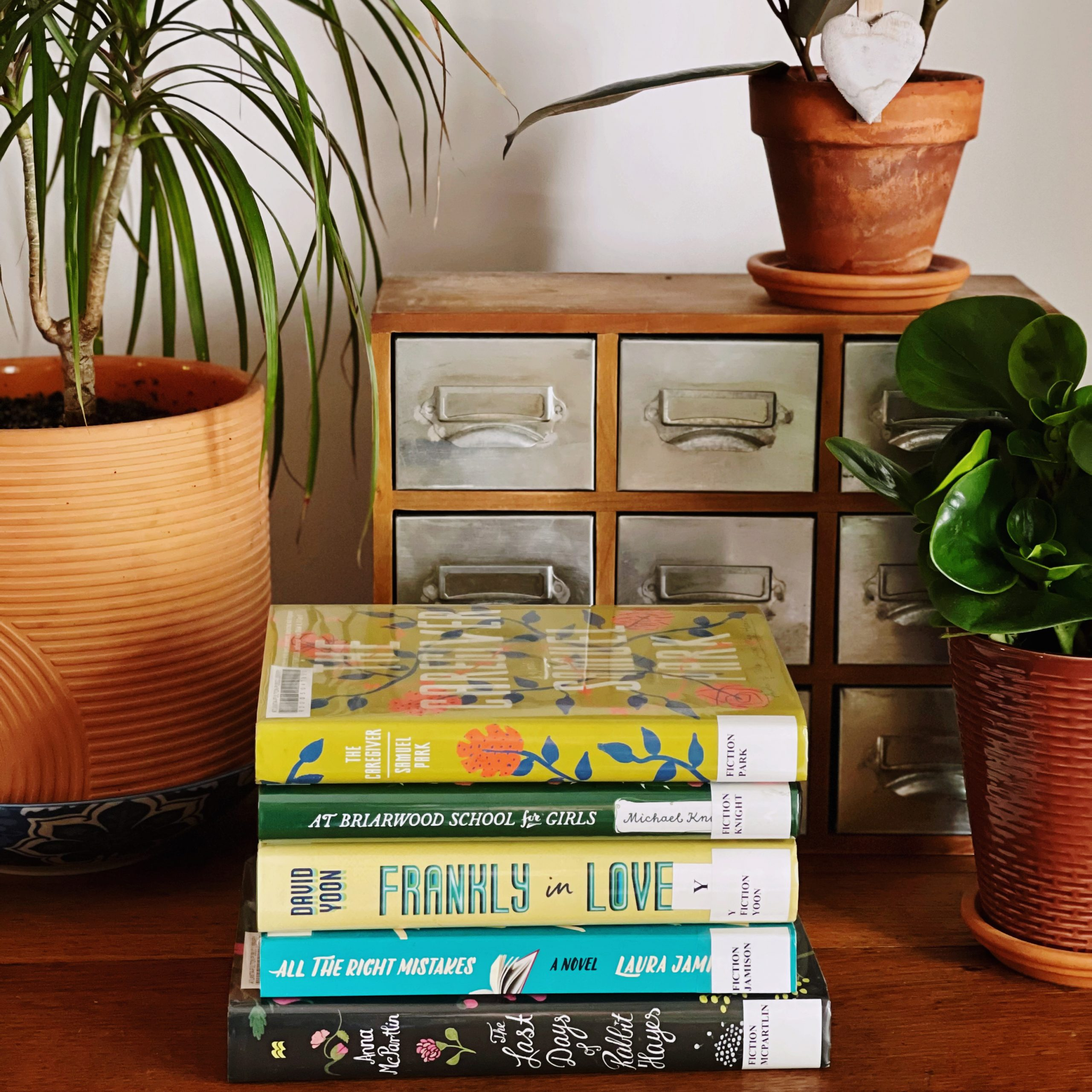 A stack of books to read this year on an end table with plants and card catalog